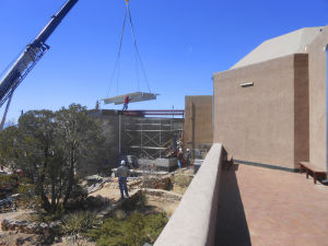 Photo by Paul Weideman A crane lowers a pre-stressed concrete double-T joist for the new building on March 20.