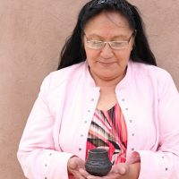 Dolores Curran holding a small pot.